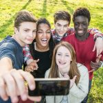 Group of multiethnic teenagers taking a selfie at park